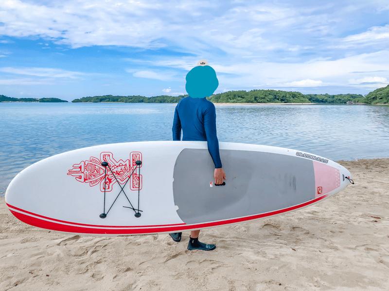 SUPボードを持ってビーチに立つ